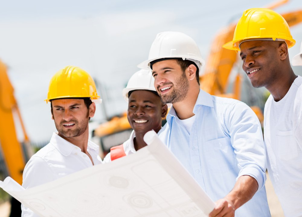 Engineers working on a building site holding a blueprints